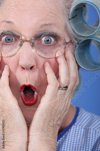 Shocked old lady wearing hair rollers