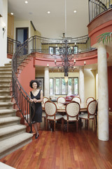 Woman standing by staircase in house
