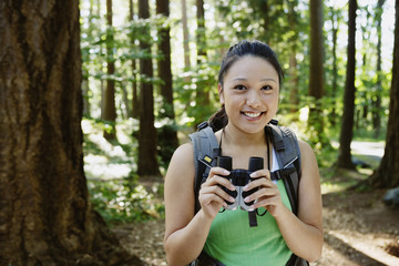 Woman with binoculars in forest