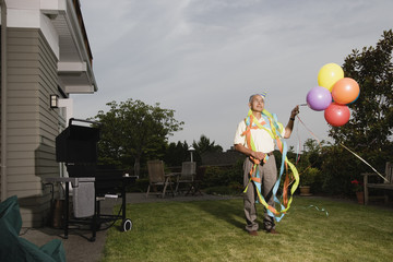 Portrait of elderly man wearing birthday hat and streamers and holding balloons