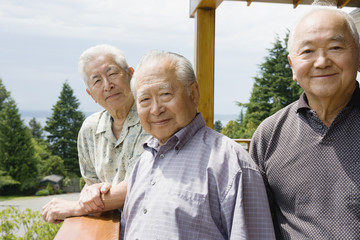 Portrait of three elderly men standing outside