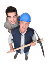 high angle shot of apprentice and senior mentor holding pickaxe