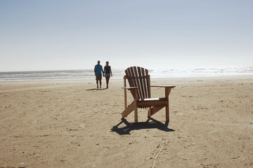 Empty chair with couple walking on beach