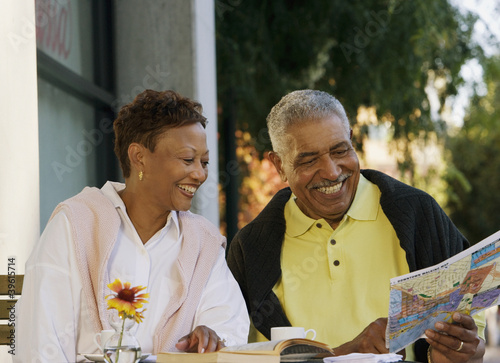 Senior couple looking at map while sitting at table