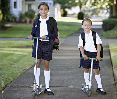 Portrait of sisters wearing uniforms on scooters