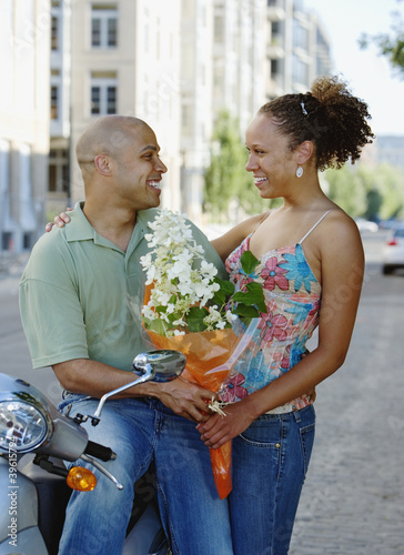 Couple looking at each other with bouquet of flowers