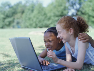 Two girls lying in park with laptop