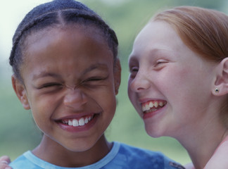 Close up portrait of two girls giggling