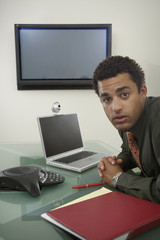 Young businessman with laptop and flat screen