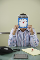 Office worker holding clock in front of face