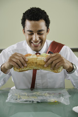 Businessman eating big sandwich