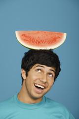 Man balancing watermelon slice on head