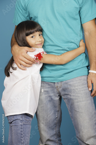 Young girl hugging torso of young man
