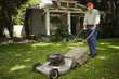 Portrait of elderly man mowing lawn