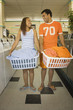 Couple carrying baskets of clothes in laundromat