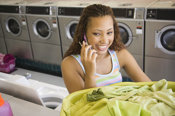 Woman talking on phone with basket of laundry in laundromat