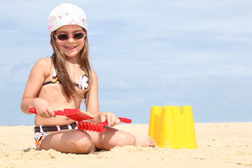 Young girl making sandcastles on a beach