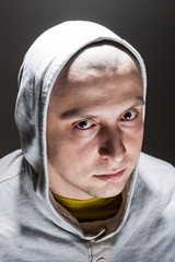 Portrait of a bold man in a hoodie