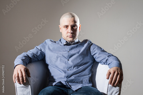 Bold man sitting in a chair