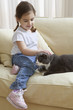 Young girl petting cat on couch