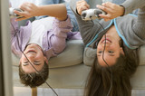 Two teenagers upside down on couch playing video games