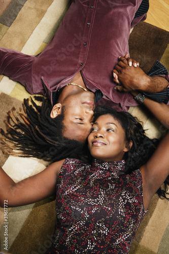 Couple laying on rug head to head