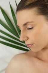 Woman asleep against a green plant