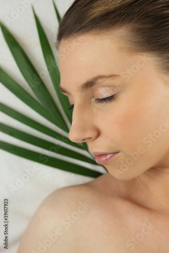 Woman asleep against a green plant