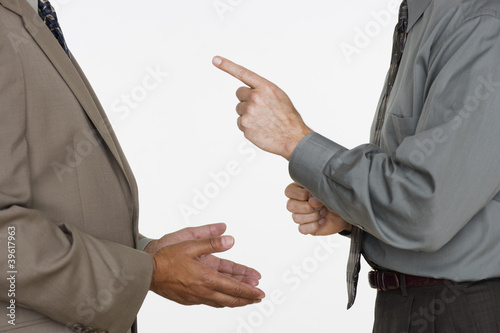 Mid section of two businessmen facing each other with hands gesturing