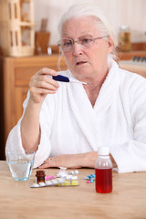 Elderly woman taking her temperature