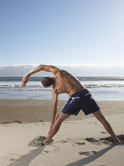 Rear view of man exercising at beach