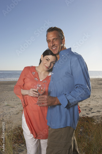 Portrait of couple at beach hugging with wine glasses