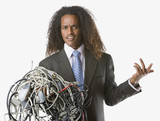 Businessman holding tangled computer cords