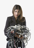 Businesswoman holding tangled computer cords