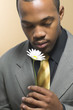 Man in suit holding daisy