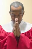Man in choir robe praying