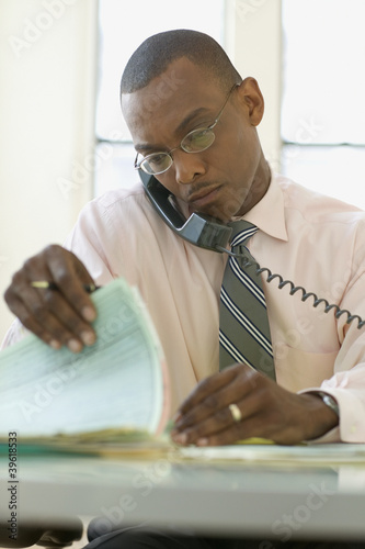 Businessman reading papers while talking on phone