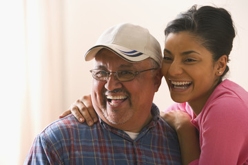 Portrait of young adult woman with her father laughing