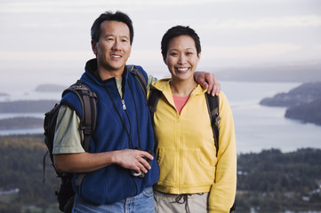 Portrait of couple hiking with valley behind them