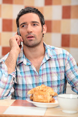 Man taking a call at breakfast
