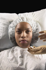African American woman in hospital cap and gown with gloved hands reaching for her