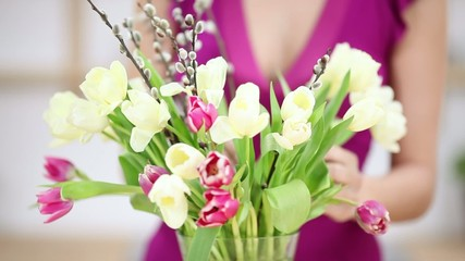 frau stellt einen strauß tulpen in eine vase
