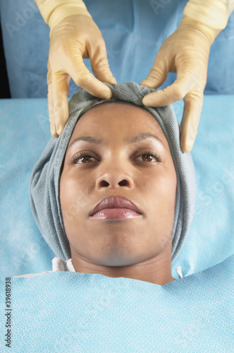 Gloved hands tying wrap on African American woman's head in hospital bed