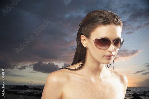Portrait of woman wearing sunglasses at sunset