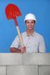 Man holding spade behind wall