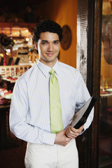 Portrait of waiter holding menus in restaurant