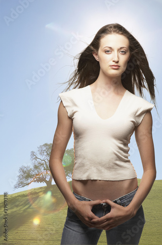 Portrait of woman standing with thumbs hooked in jeans