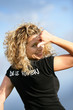 Woman stood outdoors pointing at logo on back of t-shirt