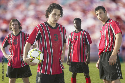 Soccer players posing for the camera on pitch