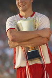 Male soccer player triumphantly hugging trophy